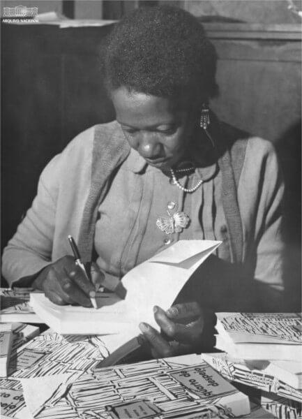 """Carolina Maria de Jesus assinando seu livro """"Quarto de Despejo"""". (Reprodução: Arquivo Nacional / Domínio Público)"""