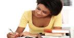 Aluna escreve ao lado de livros