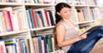 Moça lê livro em biblioteca