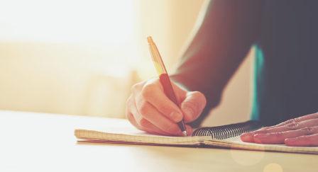 mão escreve no caderno