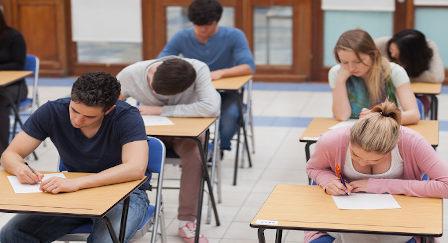 Alunos em sala de aula escrevendo