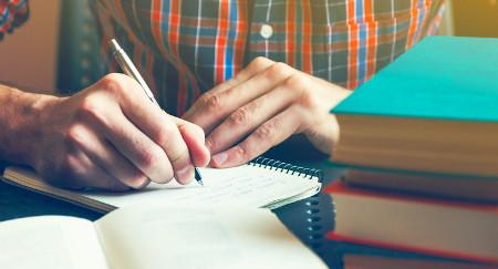 homem escrevendo em caderno com livros ao redor